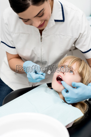 cute kid examined by dental assitant