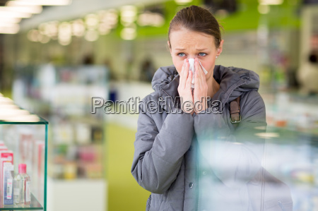 young woman blowing her nose while