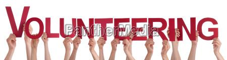 hands holding red straight word volunteering