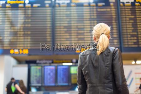 female traveller checking flight departures board