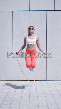 energetic young woman exercising with jumping