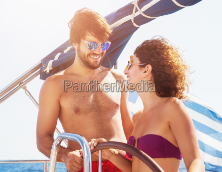 cheerful couple driving sailboat