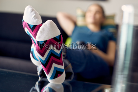 woman with feet on table watching