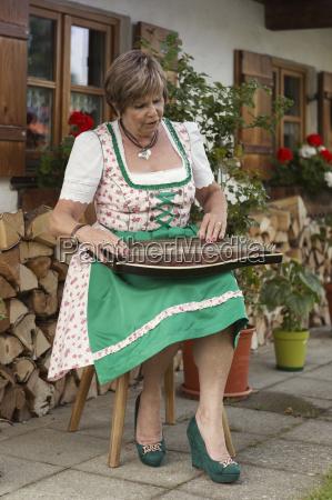 senior woman in dirndl dress plays