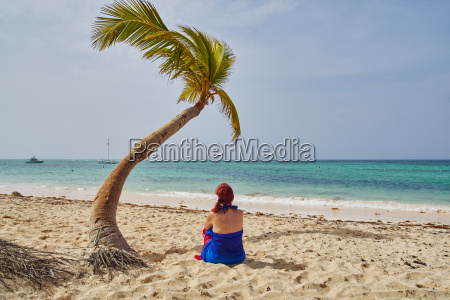 woman sitting under a coconut tree