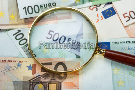 magnifying glass over banknote