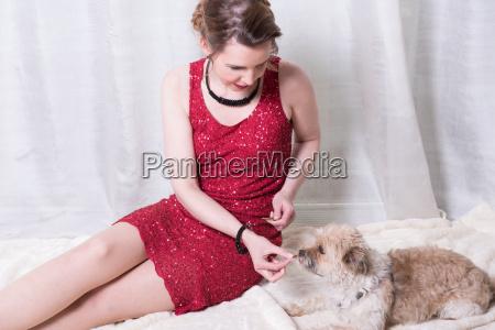 woman in red dress feeding dog