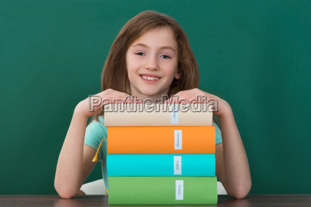 girl sitting at desk with stack