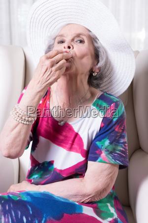 active female senior eating strawberry