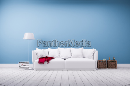 couch and standard lamp against blue