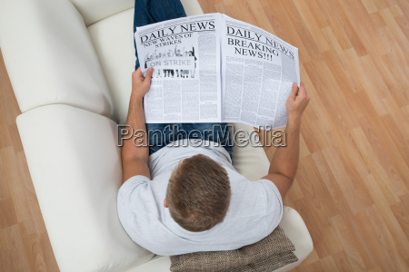 man reading newspaper at home