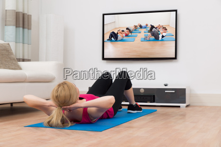 woman exercising while watching television