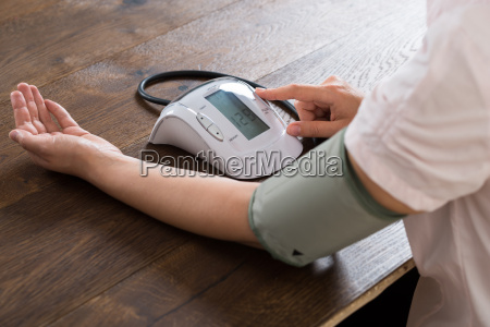 close up of businesswoman measuring blood