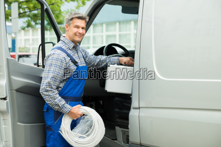 worker with toolbox and cable entering