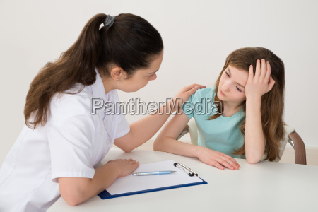 doctor comforting patient at table