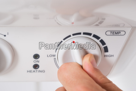 person turning the knob of electric