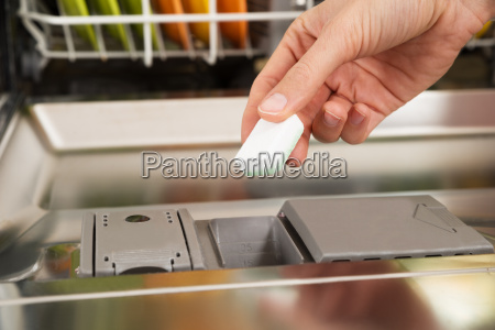 person hands putting dishwasher tablet in
