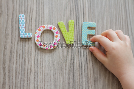 child is writing word love from