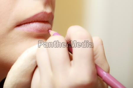 makeup artist applying cosmetic with pencil