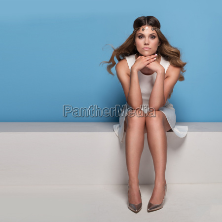 pretty woman sitting down wearing dress