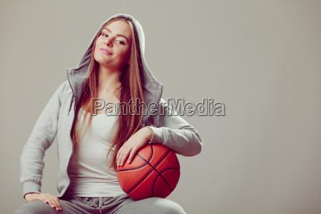 sporty teen girl in hood holding