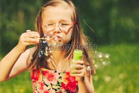 happy little girl child blowing bubbles