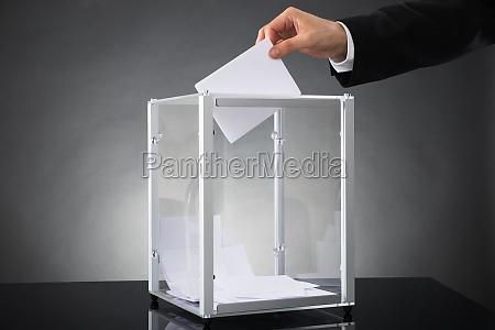 businessperson putting ballot in box