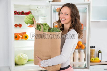 woman holding shopping bag with vegetables