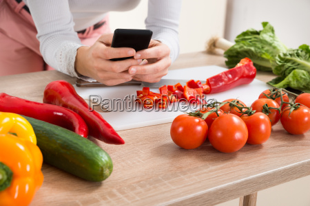 woman with mobile phone and vegetables