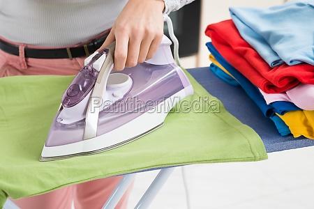 female hands ironing t shirt
