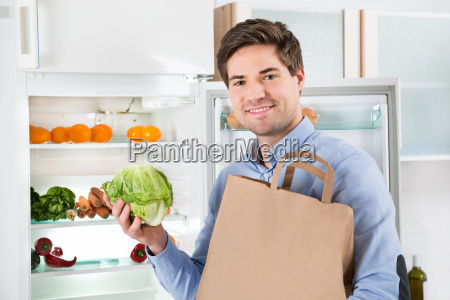 man with grocery bag standing near