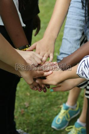 multicultural team keeps hands together