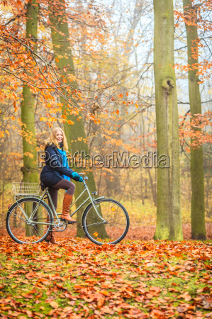 happy active woman riding bike in