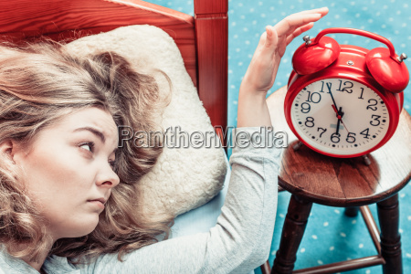 woman waking up turning off the