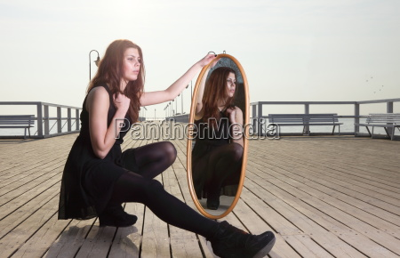 thoughtful woman looks at the reflection