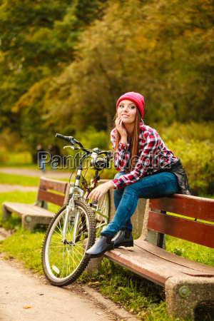 girl relaxing in autumnal park with