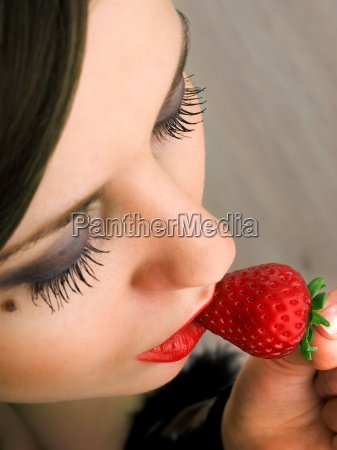 young woman eating strawberry young woman