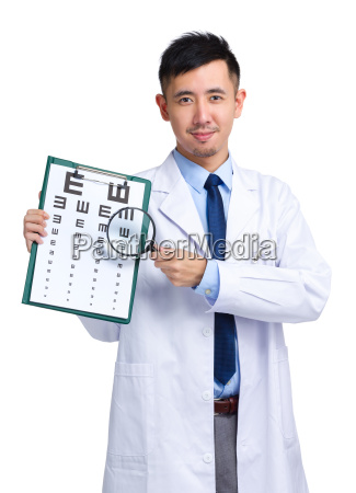 optician with eye chart and magnifying