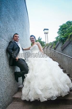 newlyweds posing on stone steps