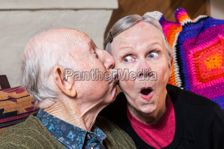 elderly gentleman kissing elderly woman on