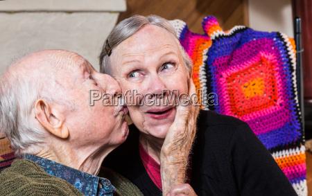 elderly gentleman kissing elderly woman on