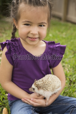 a young girl holding a small