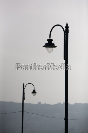 two arched street lamps silhouetted against