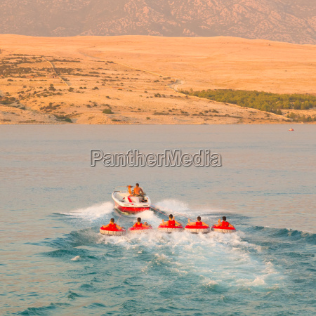 kids tube riding tawed by speedboat