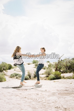 two woman holding hands dancing in