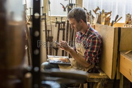 an antique furniture restorer sitting using