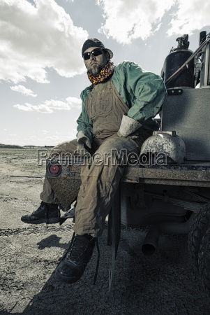 a welder seated on a truck