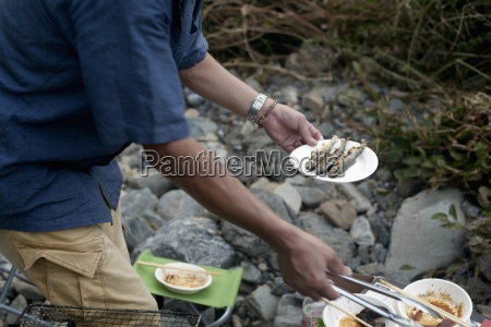 man holding a plate of grilled