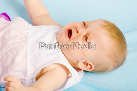 crying baby lying on plaid