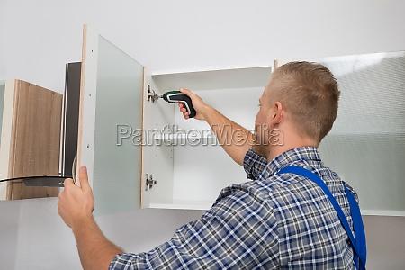 carpenter drilling in cabinet